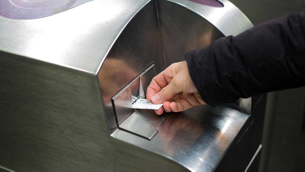Personne validant un ticket de métro dans les transports en commun